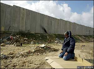 Muslim man praying at foot of Israel security wall