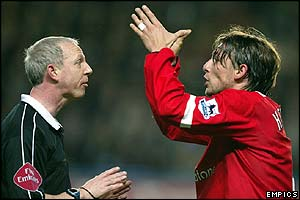 Referee Neale Barry books Manchester United's Gabriel Heinze for a foul on Didier Drogba