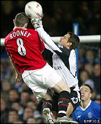 Wayne Rooney is challenged by Chelsea's goalkeeper Carlo Cudicini