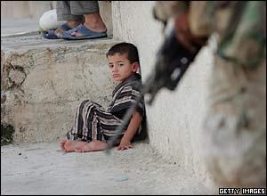 Iraqi boy watches US marine holding a rifle