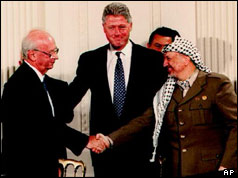 Yitzhak Rabin and Yasser Arafat shake hands in front of Bill Clinton