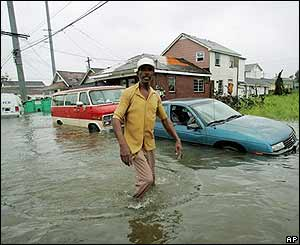 Elbert Curtis de New Orleans, camina por la calle inundada de su casa