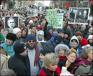 Protesters hold anti-Bush signs along the route of US President George W Bush's second term inauguration parade