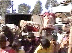Pilgrims in Wai fleeing the temple complex carrying their belongings