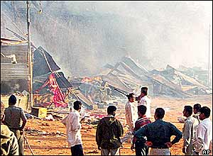 Crowds look on at burning buildings in the temple complex