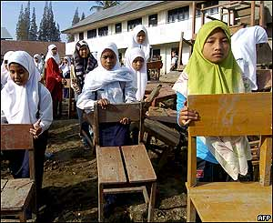 Acehnese students carry chairs during the first day of school in Banda Aceh, 26 January 2005.