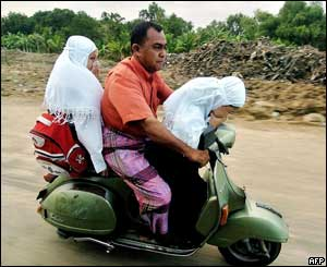 Two children cover their noses as they are driven past a mass grave on their way to school in Banda Aceh, 26 January 2005.