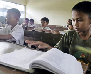 Romi Saputra, 10, right, looks through his school books during class,  Jan. 26, 2005