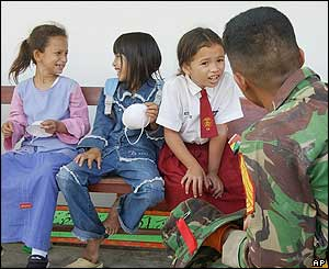 Rifa Yazira, 9, second from right, talks with an Indonesian soldier at SD Kartika primary school, Wednesday, Jan. 26, 2005