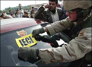 A US soldiers places an authorisation sticker on an election official's car in Jisr Diala south of Baghdad