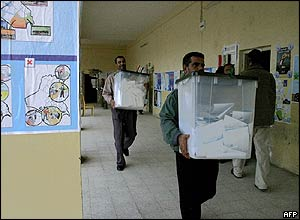 Iraqi election workers in Basra carry ballot boxes