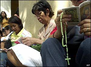 Filipino Catholics pray outside the Redemptorist church, Baclaran, Manila