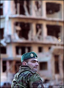 Damaged buildings behind a Lebanese security force member