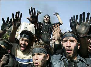 Hariri supporters with their hands stained black from burning tyres shout anti-Syrian slogans in Sidon