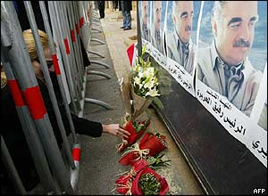 Woman lays flowers at a memorial site outside the Beirut home of former Prime Minister Rafik Hariri