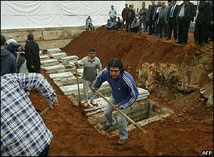 Workers prepare the graves on land adjacent to Muhammad Amin Mosque