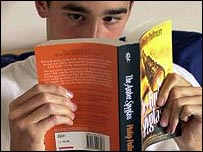 A boy reading Philip Pullman's The Amber Spyglass