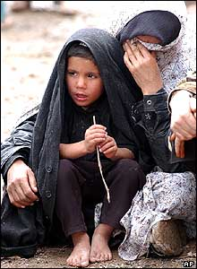 A woman cries as she sits with a child in Dahuyeh