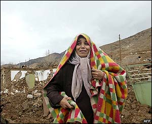 A woman cries in front of the rubble of destroyed homes in the village of Dahuyeh