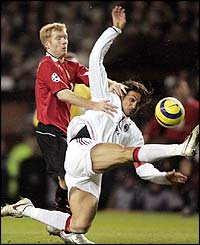 Manchester United's Paul Scholes challenges Paolo Maldini