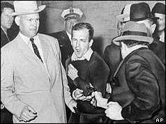 Jack Ruby with gun pointing at Lee Harvey Oswald, flanked by police officers