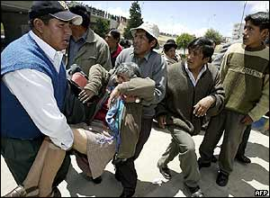 Demonstrators carry away woman affected by tear gas in El Alto in protest against French water consortium