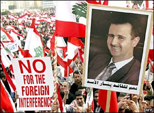 Protesters wave a picture of Syrian President Bashar al-Assad during a pro-Syria rally