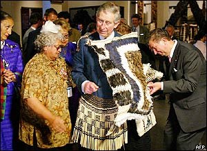Maori elders try to fit Prince Charles with a grass skirt