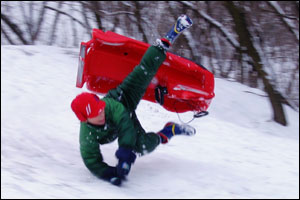Boy falling off of bobsled.