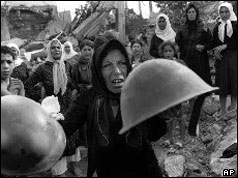 Palestinian survivors show helmets of those they say attacked them at memorial service on 27 September 1982
