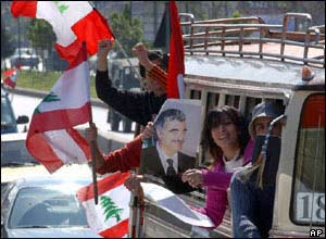 Protesters in a minivan holding flags and a picture of slain Prime Minister Rafik Hariri