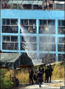 Detainees cheer as a fire truck sprays water on them to lessen the effect of tear gas  - 15/3/05