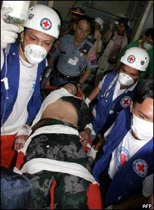 Red Cross staff carry a wounded Filipino policeman  - 15/3/05