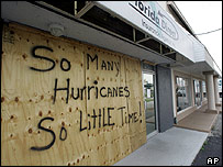 "An insurance company in Florida is boarded up with the words: ""So many hurricanes, so little time"" ."