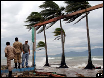 Hondurans stand in heavy winds.