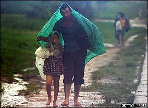 A Cuban peasant family walk in heavy rains caused by Hurricane Wilma in Havana.