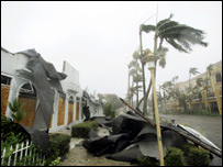Trees sway and a roof is pulled off by Hurricane Wilma in Naples, Florida.