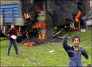 Children playing nearing a truck on fire in Iraq