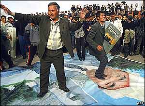 Members of the Kyrgyz opposition dance on the portrait of Kyrgyz President Askar Akayev in downtown Osh, south Kyrgyzstan, 21 March 2005
