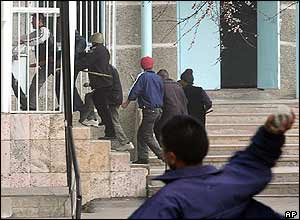 Opposition protesters enter an administrative building in Osh, Kyrgyzstan, Monday, March 21, 2005, as a demonstrator throws a stone