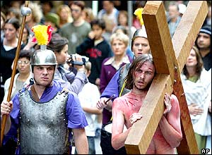 A man dressed as Jesus drags a cross down a Sydney city street during a re-enactment of the crucifixion
