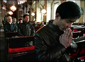 Chinese Catholics pray during a service in Beijing on Good Friday