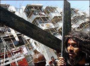 An Indian Christian in Bombay portrays Jesus Christ carrying a crucifix during a re-enactment of the Good Friday march