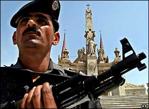 A police officer stands guard with an assault gun at the St. Patrick church in Karachi, Pakistan