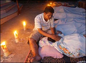 Dr Haegombowo nurses the dead body of his wife Lisbet Sihanturi at a makeshift morgue