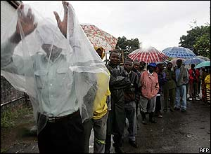 A Zimbabwean covers himself with a plastic bag as he queues to vote.