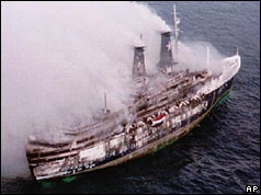 Smoke pouring from ship, damage to side