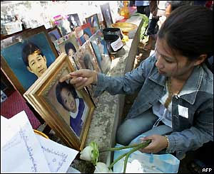 A Thai woman adjusts a portrait of a tsunami victim lined up along a wall at a Buddhist temple in Phang Nga province, 3 April 2005