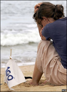 A foreign volunteer sits on the beach during the 100 days tsunami memorial at Khao Lak, 2 April 2005.