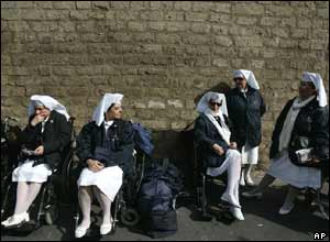 Nuns sit in wheelchairs waiting